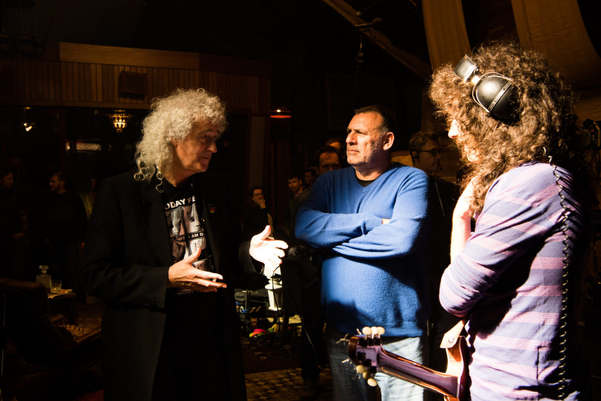 "Brian May, Producer Graham King and Gwilym Lee on the set of Twentieth Century Fox's ""Bohemian Rhapsody."""