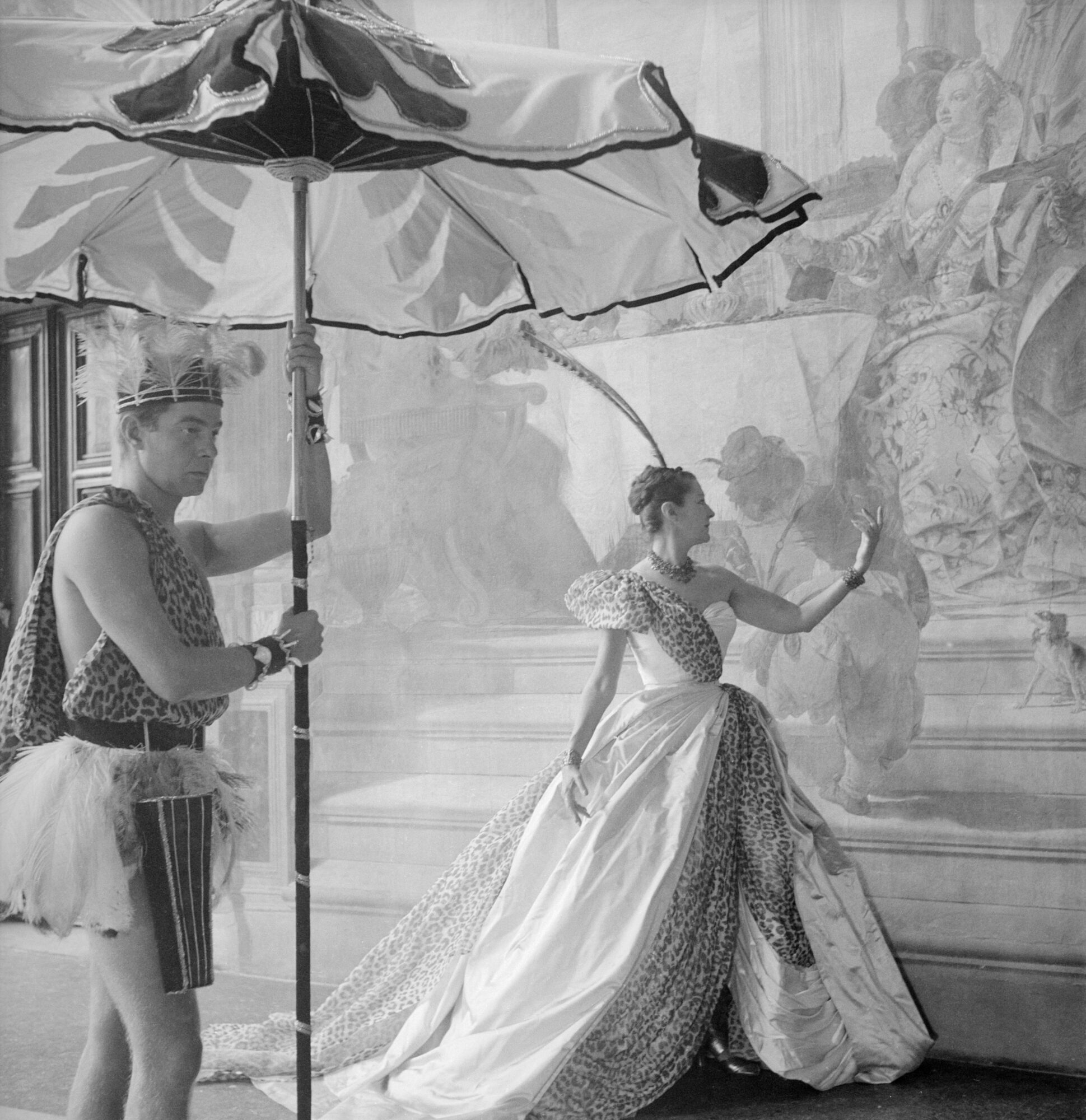 Portrait of Mrs. Reginald Fellowes dressed in a Dior costume gown for the Venetian Beistegui Ball held in the newly restored Palazzo Labia with a costumed attendant (James Caffery) holding a parasol. James Caffery, Daisy Fellowes / Cecil Beaton / Condé Nast / Shutterstock